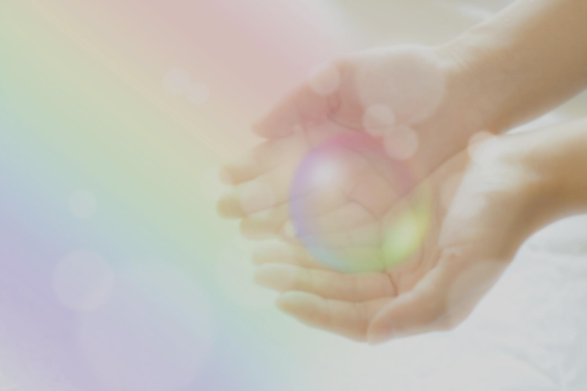 虹色の玉を持つ手